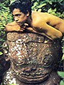 Marquesas islands. Boy and statue.